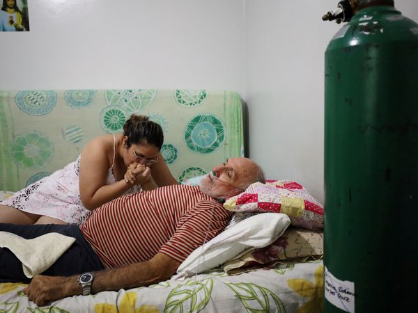Osmar Magalhaes, 68, who suffers from the coronavirus disease (COVID-19), is helped by his daughter Karoline Magalhaes at his home, where he set up his own emergency ward with air tanks due to lack of oxygen in the public health system, in Manaus, Brazil January 20, 2021. Picture taken January 20, 2021. REUTERS/Bruno Kelly