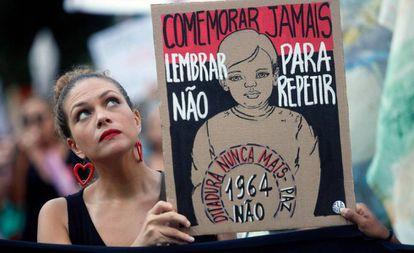 Uma manifestante segura uma placa contra a comemoração do 55º aniversário do golpe militar, no Rio de Janeiro.