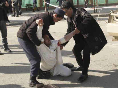 Dois homens ajudam um ferido após o atentado.