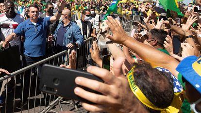 O presidente Jair Bolsonaro acena a apoiadores, aglomerados em plena pandemia de covid-19, em março.