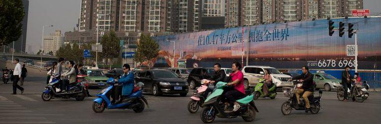 Motos elétricas cruzando uma avenida na cidade de Zhengzhou