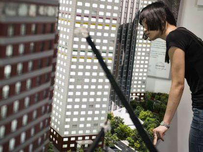 Jovem inspeciona maquetes dos diferentes edifícios padronizados construídos pela BSB.