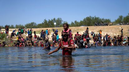 Um homem com uma menina sobre seus ombros cruza o rio Grande dos Estados Unidos para o México. Em vídeo, imagens dos migrantes na fronteira com o México.