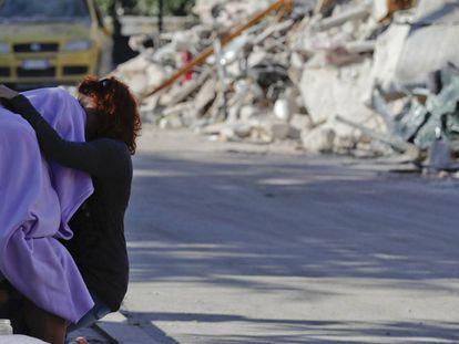 Homem e mulher se consolam em frente a uma casa em ruínas. AP