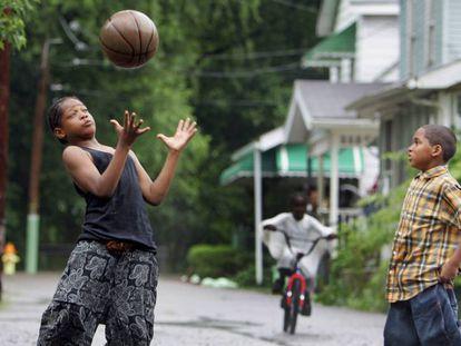 Dois garotos jogam basquete em uma rua de Akron.
