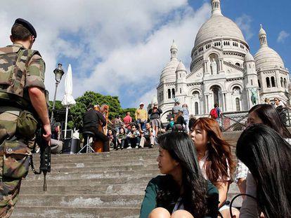 Militar em patrulha junto a um grupo de turistas coreanas, na entrada da basílica de Sacré Coeur, em Paris.