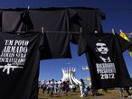 """Supporters of Brazilian President Jair Bolsonaro rally in support of loosened gun control outside the Cathedral of Brasilia, Brazil, Friday, July 9, 2021. The T-shirt at left carries the Portuguese phrase: """"An armed people will never be enslaved,"""" and the one at right features the president and the upcoming election year. (AP Photo/Eraldo Peres)"""