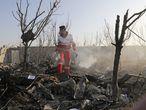 Un trabajador de emergencias camina entre los restos del avión siniestrado, este miércoles cerca de Teherán (Irán).