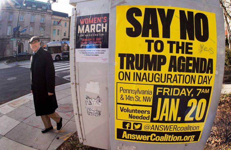 Dois cartazes sobre marchas contra Trump, no centro de Washington