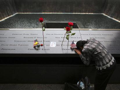 Uma mulher chora junto ao nome de seu marido, uma das vítimas do atentado de 11 de Setembro.
