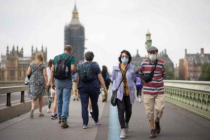 Várias pessoas cruzam a ponte de Westminster em Londres na segunda-feira.