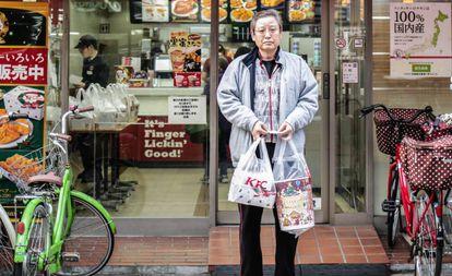 Um homem sai de um KFC em Tóquio (Japão) com seu menu natalino.