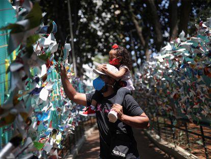 Pai e filha colocam um moinho de vento em homenagem às vítimas da covid-19, em São Paulo.