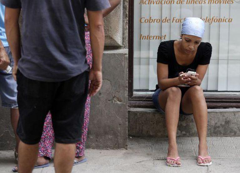 Uma mulher utiliza seu celular nas ruas de Havana.
