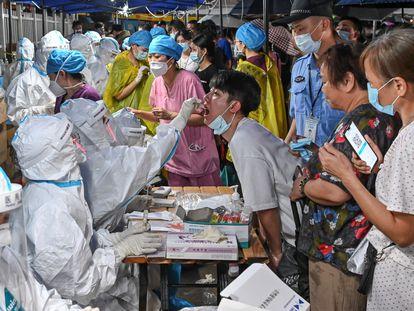 Agentes sanitários fazem exames maciços de covid-19 em Cantão (China), no domingo.