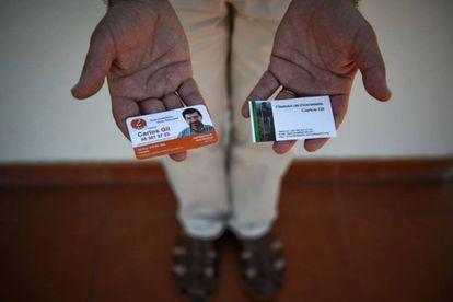 Carlos Gil mostra seus cartões de trabalho: agente imobiliário (à esquerda) e pagador de promessas.