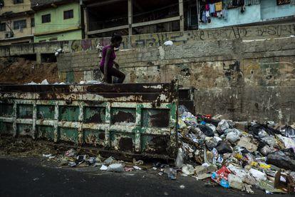 Moradores do o bairro de Petare procuram comida em um contêiner de lixo, em março de 2019 em Caracas, Venezuela.