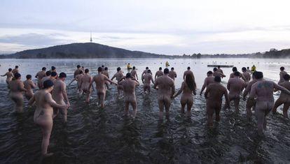 Dezenas de pessoas participam nuas nesta quinta-feira do banho de caridade pelo solstício de inverno no lago Burley Griffin, em Canberra (Austrália).