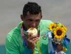 Isaquias Queiroz dos Santos, of Team Brazil, bites his gold medal during the medal ceremony for men's canoe single 1000m final at the 2020 Summer Olympics, Saturday, Aug. 7, 2021, in Tokyo, Japan. (AP Photo/Lee Jin-man)