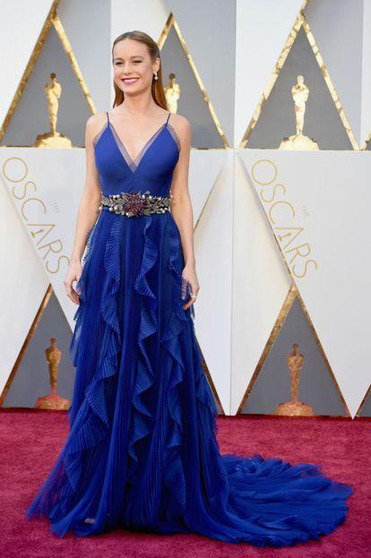 """Brie Larson, de 26 anos, é uma das atrizes do momento. Indicada como melhor atriz por seu trabalho em 'O quarto de Jack', já levou o Globo de Ouro, o BAFTA e o SAG. Esta noite, vai à cerimônia com um vestido azul noite com um pronunciado decote em """"V"""" e cinto de pedraria, da italiana Gucci.  Em suas aparições no tapete vermelho, a estrela costuma optar por designs minimalistas mas glamorosos. A atriz, que já confiou seu 'look' a estilistas norte-americanos como Katherine Kidd e Wes Gordon, na entrega passada dos SAG Awards apresentou um vestido da grife italiana Versace. Na cerimônia do Oscar do ano passado escolheu um vestido vermelho vivo de Calvin Klein."""
