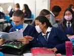 Colombian students use masks made with recyclable and biodegradable materials, following a shortage of medical mask due to the spread of the new Coronavirus, COVID-19, and the high pollution of the city, at Julio Cesar Turbay school in Soacha near Bogota, on March 11, 2020. - The World Health Organisation (WHO) declared the Coronavirus a pandemic with 118,000 cases in about 120  countries, and 4000 deaths. (Photo by Raul ARBOLEDA / AFP)