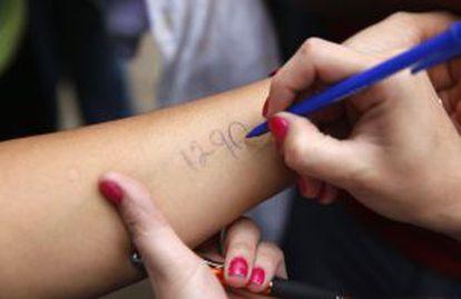 Cidadãos de San Cristóbal escrevem um número em seus braços para marcar sua vez na fila do supermercado.
