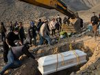 A backhoe places the coffin containing the body of Vicenta Panduro Panduro, 87, who died from COVID-19 complications, into her tomb at a cemetery in Carabayllo, Lima, Peru, Tuesday, Aug. 25, 2020. (AP Photo/Rodrigo Abd)
