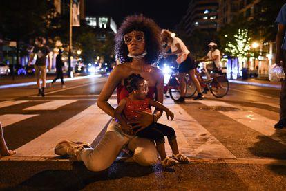 Twana Buck e sua filha Bonita, sentadas em uma rua  perto da Casa Branca, durante protestos, em 23 de junho, contra a morte de George Floyd.