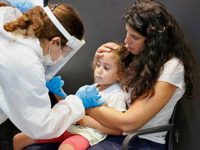 Uma menina se submete a um exame de antígenos para poder entrar em um parque temático, nesta quinta-feira, em Tel Aviv.