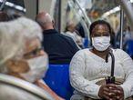 Dos pasajeras del metro de São Paulo se protegen con barbijos.