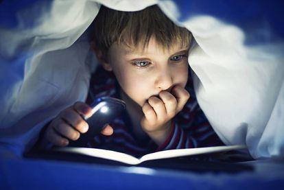 Menino lendo um livro iluminado pela luz do celular