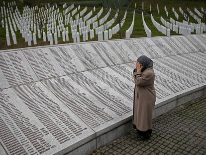 Uma mulher reza diante da placa com os nomes das vítimas de Srebrenica em Potocari (Bósnia), em 2016.