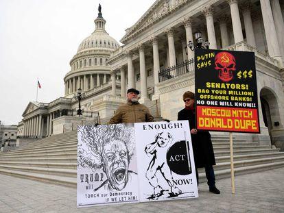 Manifestantes levam cartazes de protesto no Capitólio, na sexta-feira.