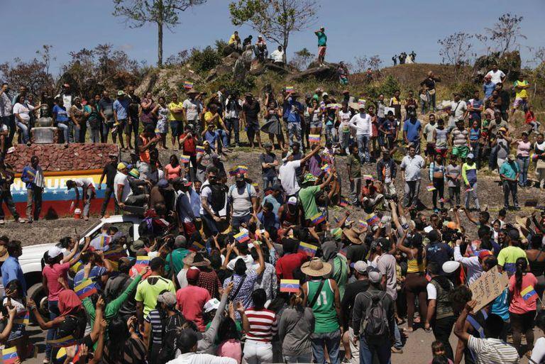 Dezenas de pessoas concentram-se na fronteira do Brasil com Venezuela.