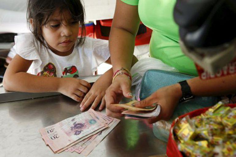 Uma criança olha enquanto sua mãe conta bolívares.