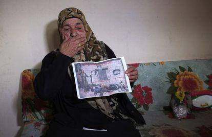 Uma sobrevivente mostra uma foto sua junto aos cadáveres de sua família.