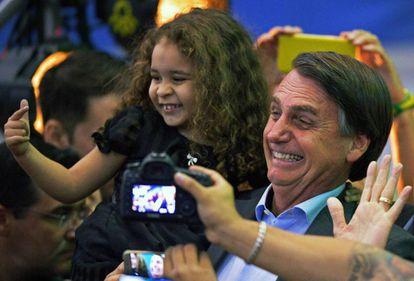 Bolsonaro, num evento em que ensinou uma criança a imitar um revólver com os dedos.