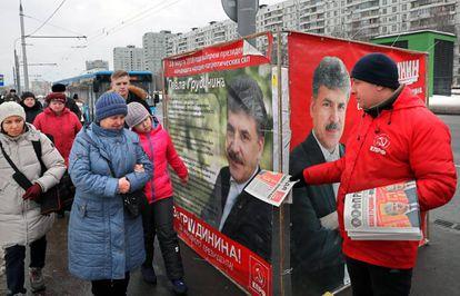Militante do Partido Comunista da Rússia distribui panfleto junto a cartazes da campanha eleitoral do candidato comunista, na última terça-feira.
