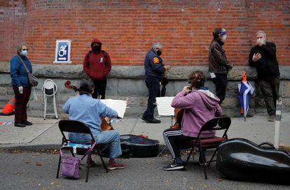 Músicos tocam violoncelo para eleitores que aguardavam para votar antecipadamente nas eleições dos EUA em Nova York, em 27 de outubro.