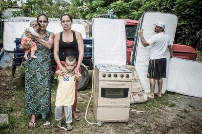 Ana Paula (à esquerda) com filhos e amiga na escola que recebe doações para desabrigados na zona leste de São Paulo.