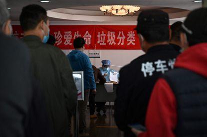 Um agente de saúde registra, na quinta-feira, cidadãos que querem receber a vacina contra a covid-19 em um centro comunitário de Pequim.