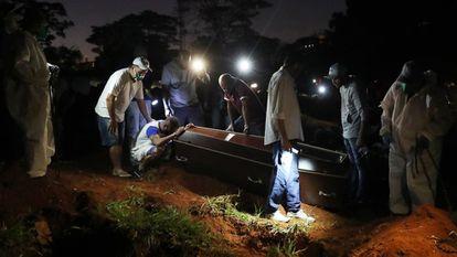 Um homem chora junto ao caixão de seu pai, morto em decorrência do coronavírus, no cemitério da Vila Formosa em São Paulo.