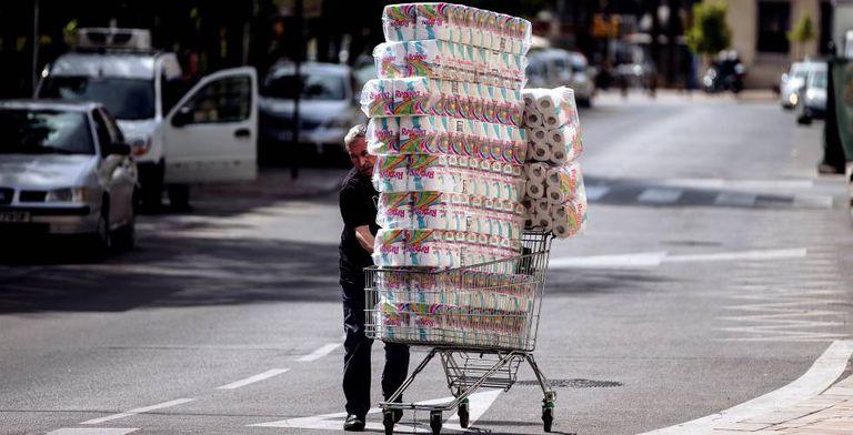 Um repositor empurra um carrinho com papel higiênico até uma loja em Málaga.