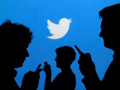 Pessoas com celulares em frente à logo do Twitter.