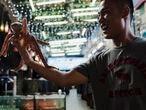 Um vendedor de pescado segura um polvo vivo nas mãos para oferecer às pessoas passam por sua loja. Na praia de Dapeng Jiaochangwei. Província de Guangdong, sul da China. Em  15 de agosto de 2021.