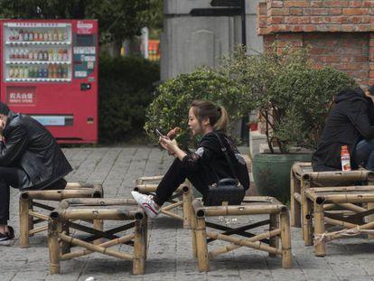 Três pessoas interagindo em Wuhan, na China.