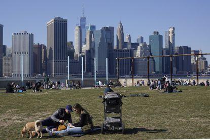Cidadãos relaxam no bairro nova-iorquino do Brooklyn, com Manhattan ao fundo, no domingo passado.