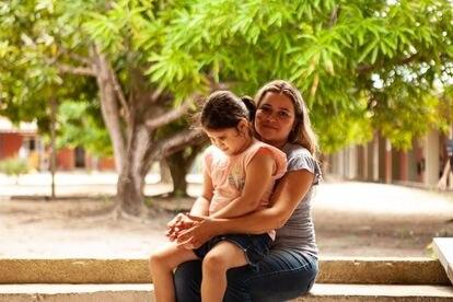 Débora Oliveira e a filha, Nauany Sales, no colo.