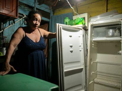 Rosilde Ferreira das Neves, 49 anos, mostra a geladeira queimada, e vazia, resultado do apagão em Macapá.