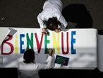 Staff members of the private school Institut Sainte Genevieve prepare a welcoming banner on May 7, 2020, in the French capital Paris as the schools in France are to gradually reopen from May 11, when a partial lifting of restrictions due to the Covid-19 pandemic caused by the novel coronavirus will come into effect. (Photo by PHILIPPE LOPEZ / AFP)